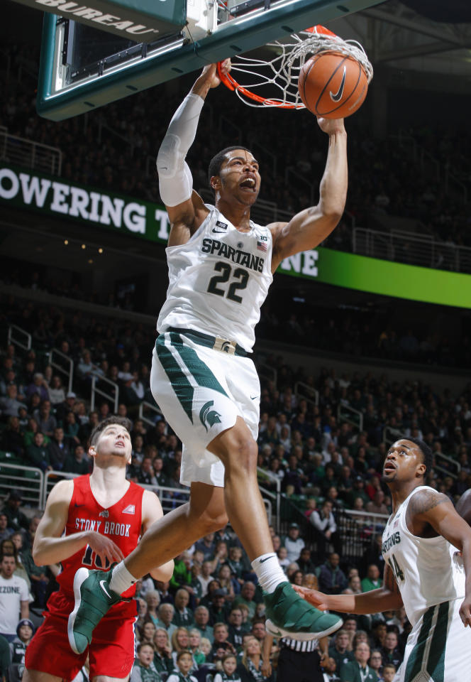 Michigan State's Miles Bridges (22) dunks off an alley-oop against Stony Brook's Jordan McKenzie, left, during the first half of an NCAA college basketball game, Sunday, Nov. 19, 2017, in East Lansing, Mich. (AP Photo/Al Goldis)