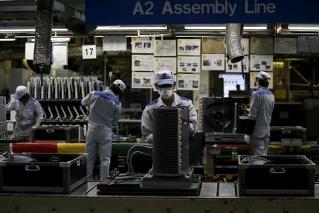 FILE PHOTO: Daikin Industries Ltd employees work the production line of outdoor air conditioning units at the company's Kusatsu factory in Shiga
