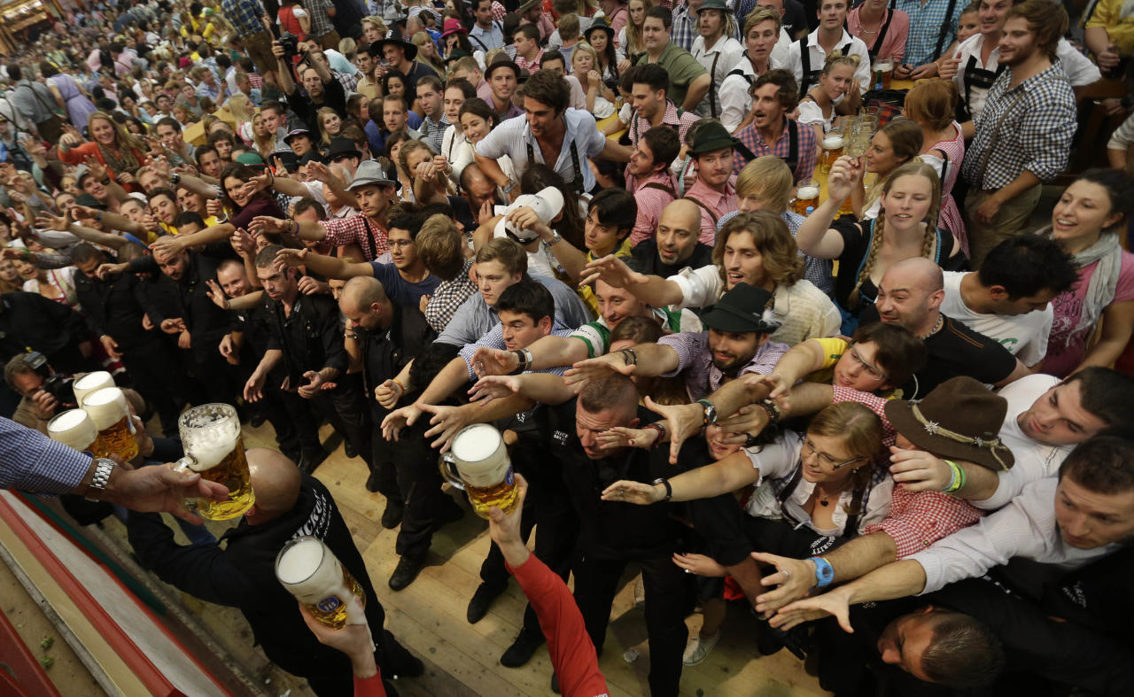 """People stretch out to reach beer mugs in the Hofbraeuhaus tent after the opening of the famous Bavarian """"Oktoberfest"""" beer festival in Munich, southern Germany, Saturday, Sept. 22, 2012. The world's largest beer festival, to be held from Sept. 22 to Oct. 7, 2012 will see some million visitors. (AP Photo/Matthias Schrader)"""
