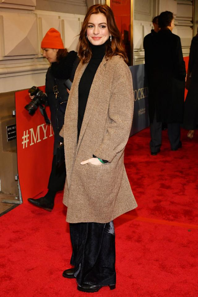 <p><strong>13 December </strong>Anne Hathaway wrapped up in a stylish beige coat and black wide-leg trousers. </p>