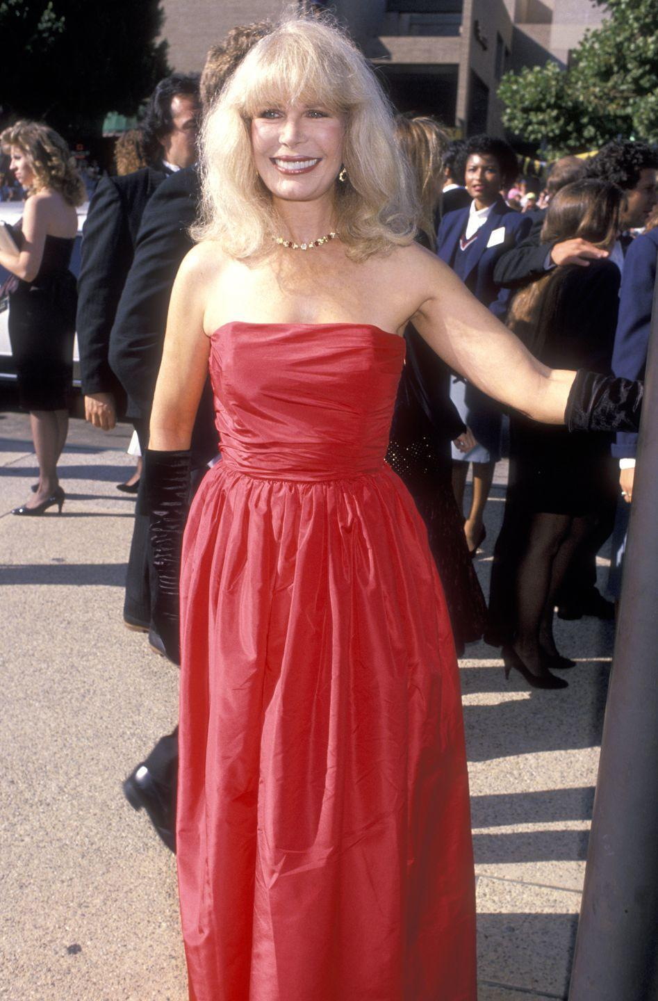 """<p>Star of """"M*A*S*H,"""" Swit stunned in a floor-length red dress and elegant black gloves. </p>"""