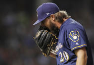 Milwaukee Brewers' Wade Miley yells into his glove as he walks off the field at the end of the first inning of a baseball game Monday, Sept. 10, 2018, in Chicago. (AP Photo/Jim Young)