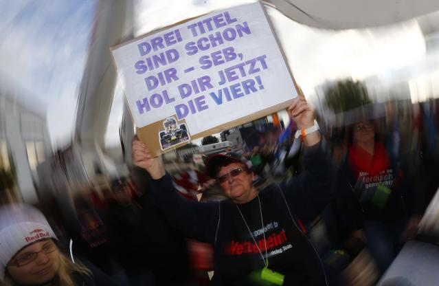"A supporter of Germany's Red Bull Formula One driver Sebastian Vettel holds up a placard reading ""three titles are yours, Seb go for the fourth one"" during a public viewing session of the Formula One Grand Prix of India in Dehli, in Vettel's hometown of Heppenheim, southwestern Germany, October 27, 2013. REUTERS/Kai Pfaffenbach (GERMANY - Tags: SPORT MOTORSPORT)"