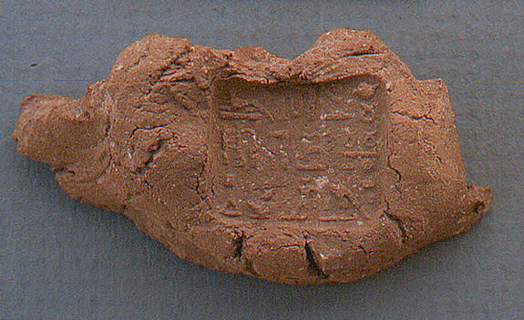 An inscribed seal, used to hold the strings or binding of a papyrus scroll, was found near the fragments of a collar worn by a mummy. The inscription identifies the seal as being for Padihorwer, a man from the town of Qus who worked as an under