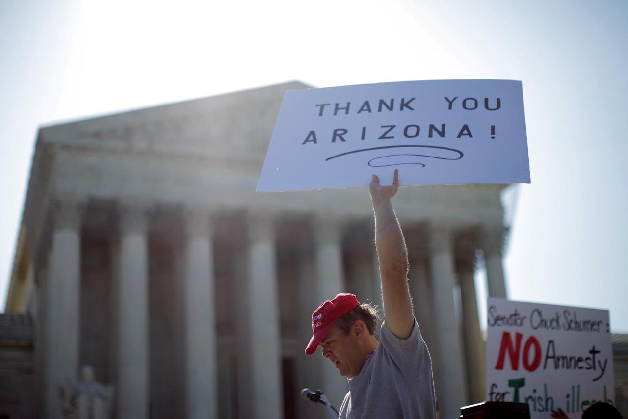 "A supporter of Arizona's ""show me your papers"" immigration law, who declined to be identified, demonstrates in front of the Supreme Court in Washington, Wednesday, April 25, 2012. (AP Photo/Charles Dharapak)"
