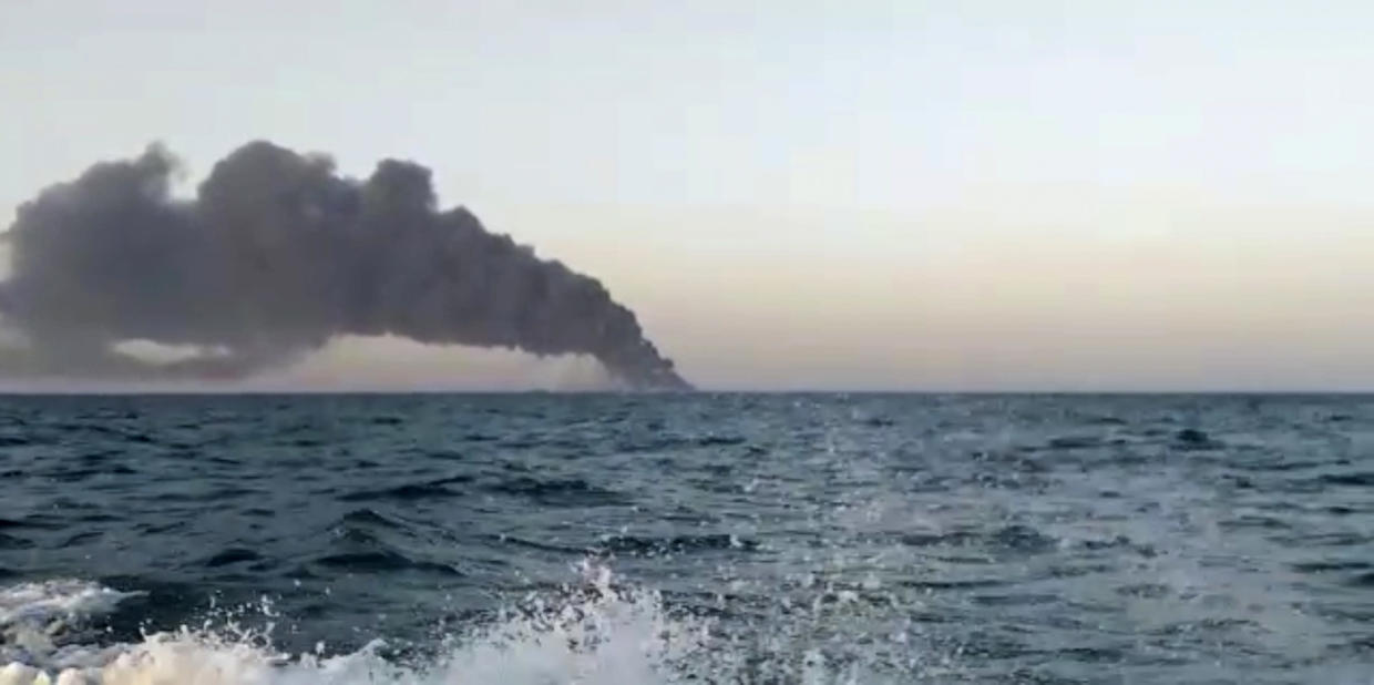 This image made from a video released on Wednesday, June 2, 2021 by Asriran.com, shows smoke rising from Iran's navy support ship Kharg in the Gulf of Oman. Kharg, the largest warship in the Iranian navy caught fire and later sank Wednesday in the Gulf of Oman under unclear circumstances, semiofficial news agencies reported. (Asriran.com via AP)