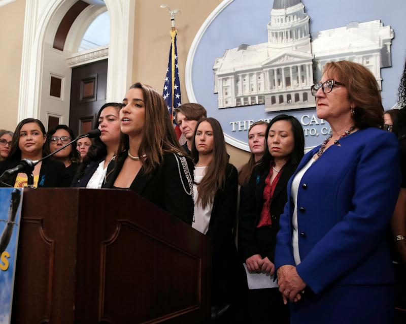 Olympic Gold Medalist Aly Raisman, foreground left, joined by dozens of victims of sexual assault by USC's Dr. George Tyndall, speaks in support of a measure by Assemblywoman Eloise Gomez Reyes, D-,San Bernardino, right, that would extend the statute of limitations to file civil lawsuits against Tyndall, at the Capitol Tuesday, April 23, 2019, in Sacramento, Calif. Tyndall, who was an OB GYN at the USC health center, is accused of sexually assaulting and abusing women under his care for nearly three decades. Raisman was assaulted by former USA Gymnastics doctor Larry Nassar. (AP Photo/Rich Pedroncelli)