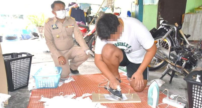 A worker reenacts ironing the masks under police instruction in the Thai province of Saraburi.