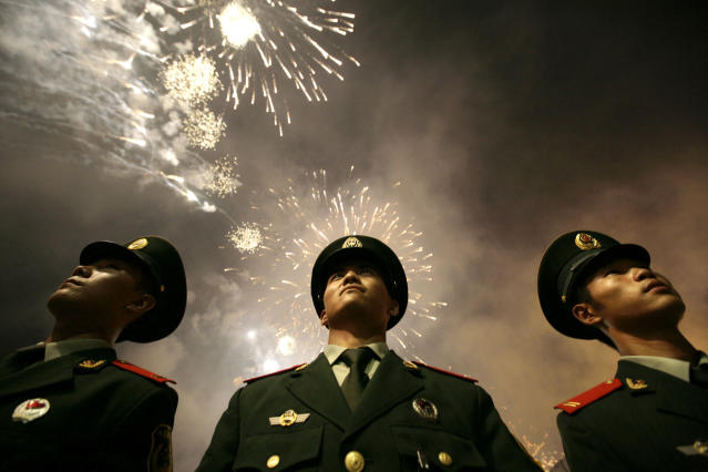 <p>Chinese paramilitary police officers stand next to the National Olympic Stadium, also known as the Bird's Nest, during the opening ceremony of the Beijing 2008 Olympics on Aug. 8, 2008. (Photo: Oded Balilty/AP) </p>