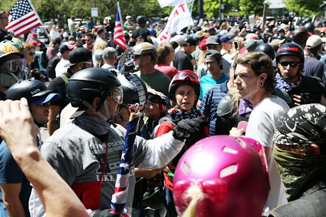 <p>An alt-right sympathizer (L) knocks the hat off an opponent's head as alt-right activists, anti-fascist protesters, and people on all sides of the political spectrum gather for a campaign rally organized by right-wing organizer, Patriot Prayer founder and Republican Senate candidate Joey Gibson in Portland, Ore., Aug. 4, 2018. (Photo: Thomas Patterson/AFP/Getty Images) </p>
