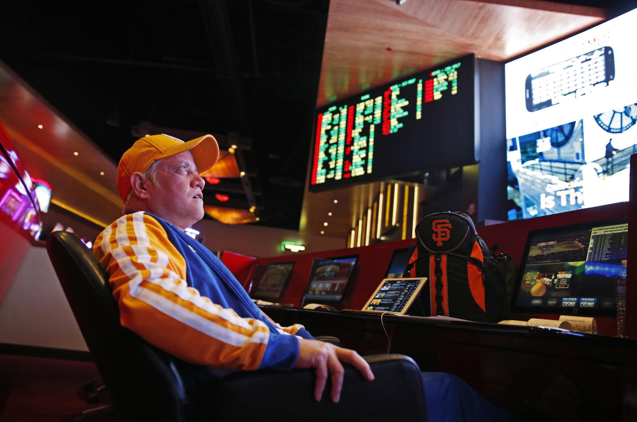 FILE – In this Jan. 14, 2015, file photo, Amado Nanalang watches basketball games while making bets at a sports book owned and operated by CG Technology in Las Vegas. The U.S. Supreme Court is set to hear arguments Dec. 4, 2017, as the state of New Jersey challenges a 1992 law forbidding state-authorized sports gambling in all but four states that met a 1991 deadline to legalize it: Delaware, Montana, Nevada and Oregon. (AP Photo/John Locher, File)