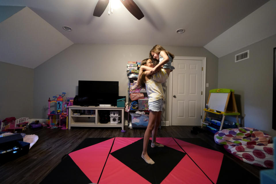Cecilia Shaffette picks up her sister Lydia in their home in Carriere, Miss., Wednesday, June 16, 2021. (AP Photo/Gerald Herbert)