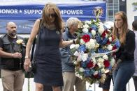 Mary Ellen Callahan, left, and Kelsey Powers, right, carry a wreath in memory of Marine Sgt. Johanny Rosario Pichardo, from Lawrence, Mass., during a ceremony at the Massachusetts Fallen Heroes Memorial, Saturday, Aug. 28, 2021, in Boston. The ceremony was held to honor the U.S. service members killed in a suicide bombing at the airport in Kabul, Afghanistan, including Rosario. (AP Photo/Michael Dwyer)