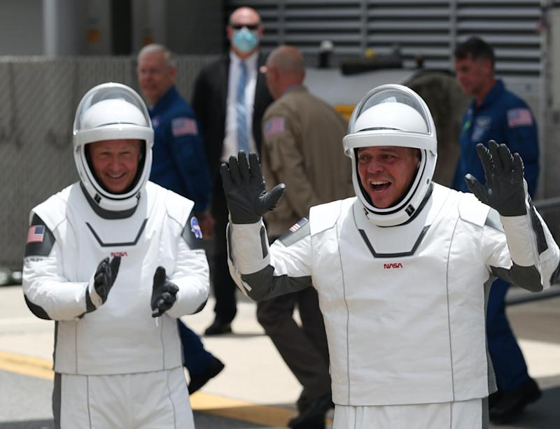NASA astronauts Bob Behnken (R) and Doug Hurley (L) walk out of the Operations and Checkout Building on their way to the SpaceX Falcon 9 rocket with the Crew Dragon spacecraft on launch pad 39A at the Kennedy Space Center on May 27, 2020 in Cape Canaveral, Florida: Joe Raedle/Getty Images