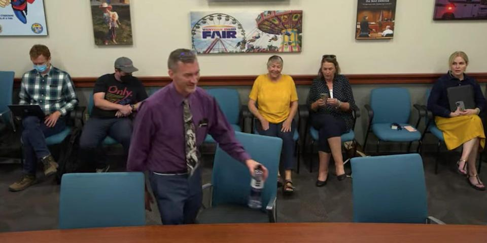 Dr Ryan Cole taking his seat to be interviewed for the CDH Board on August 9, 2021. Members of the public sit behind him.