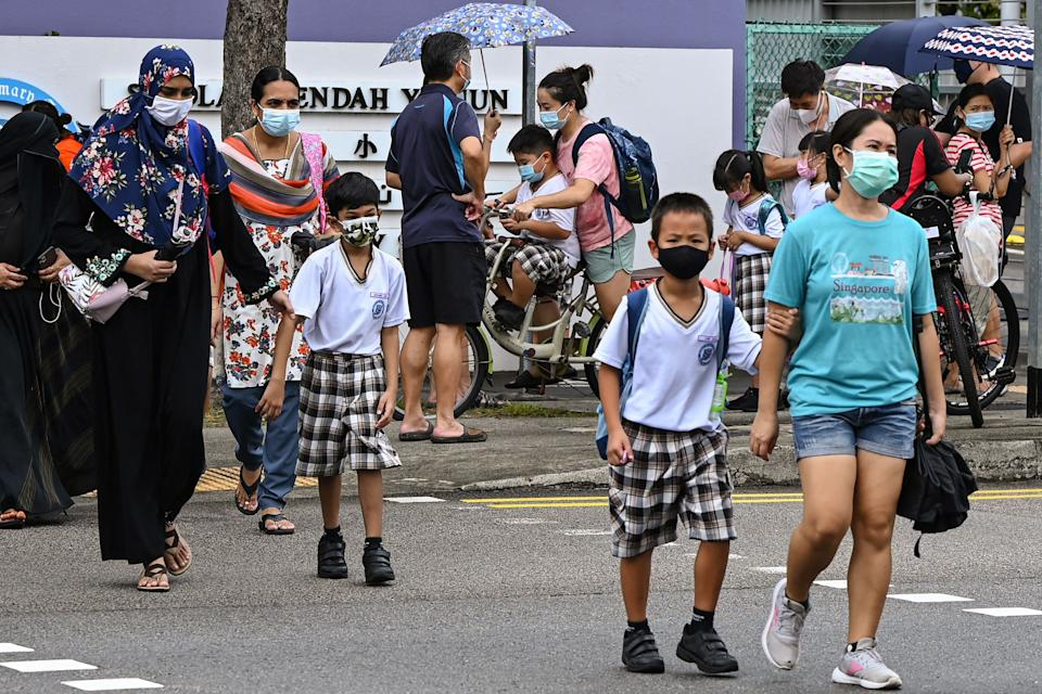 Children walk home with their guardians after school in Singapore on May 17, 2021, as the country prepares to shut all schools and switch to home-based learning until the end of the term due to a rise in the number of Covid-19 coronavirus cases. (Photo by Roslan RAHMAN / AFP) (Photo by ROSLAN RAHMAN/AFP via Getty Images)