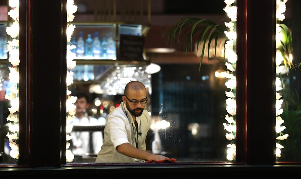 A barman at the Seven Stars pub in Brighton cleans the bar area after closing as from today pubs and restaurants will be subject to a 10pm curfew to combat the rise in coronavirus cases in England.