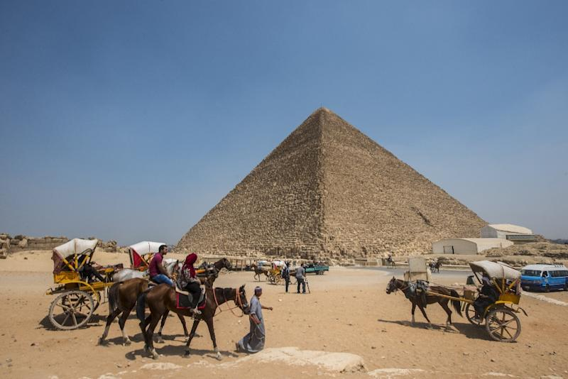 Egyptians ride their carts past the Great Pyramid of Cheops, aka Pyramid of Khufu, on August 31, 2016 on the Giza Plateau