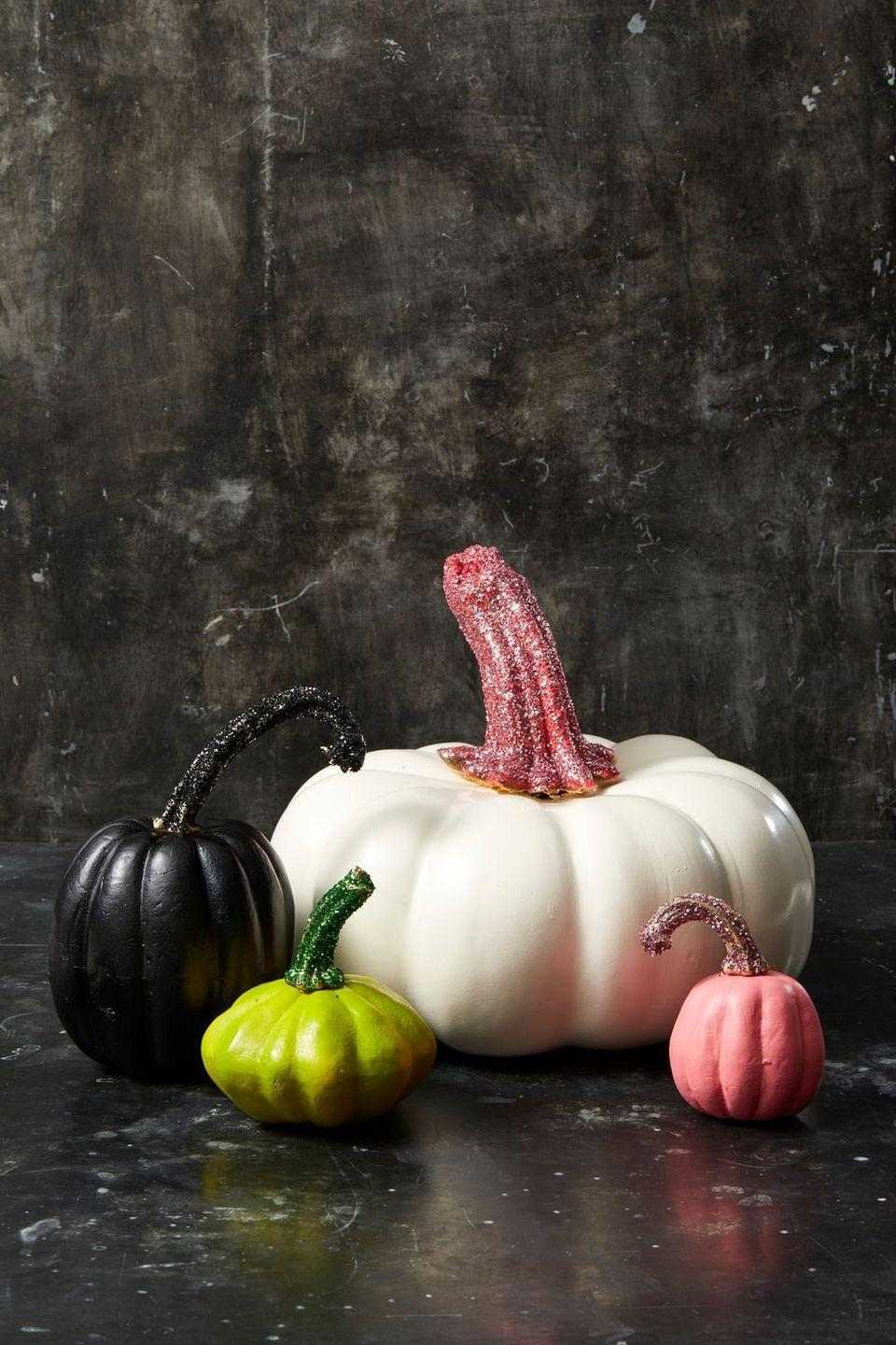 <p>Once you paint the base of the pumpkin, pick a glittery accent for the stem. Simply, dip the stem in glue and then cover it with craft glitter — either a solid shade or a unique mixture. </p>