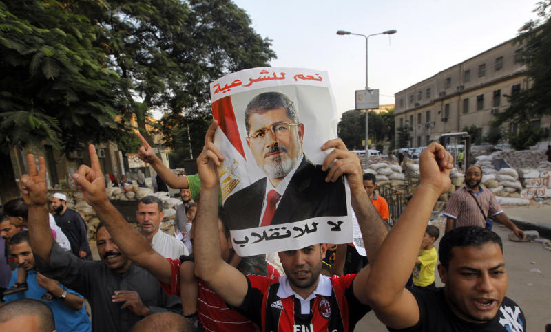 "Supporters of Egypt's ousted President Mohammed Morsi walk through makeshift barriers to a sit-in at Nahda Square, which is fortified with multiple walls of bricks, tires, metal barricades and sandbags, where protesters have installed their camp near Cairo University in Giza, southwest of Cairo, Egypt, Saturday, Aug. 10, 2013. Morsi supporters hunker down behind makeshift security barriers in preparation of a possible crackdown this week on their two main Cairo sit-ins. It comes as Egypt's leadership vows that the decision to disperse the sit-ins is irreversible. The Arabic on the poster reads, ""Yes for legitimacy, no for coup."" (AP Photo/Amr Nabil)"