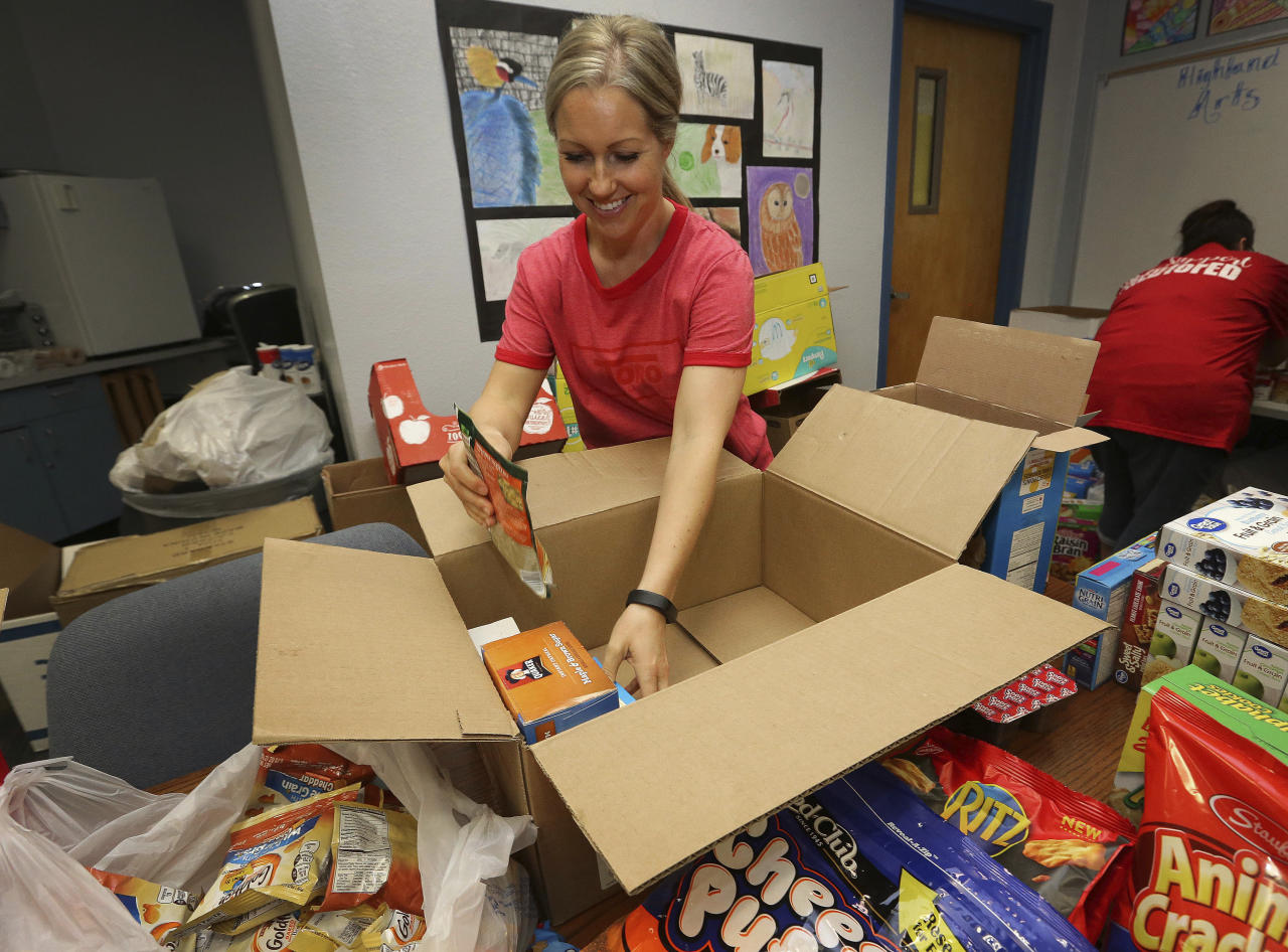 Volunteer Janae Woffinden organizes donated food for distribution to students and families on the eve of the teacher walk out Wednesday, April 25, 2018, at Highland Arts Elementary School in Mesa, Ariz. (AP Photo/Matt York)