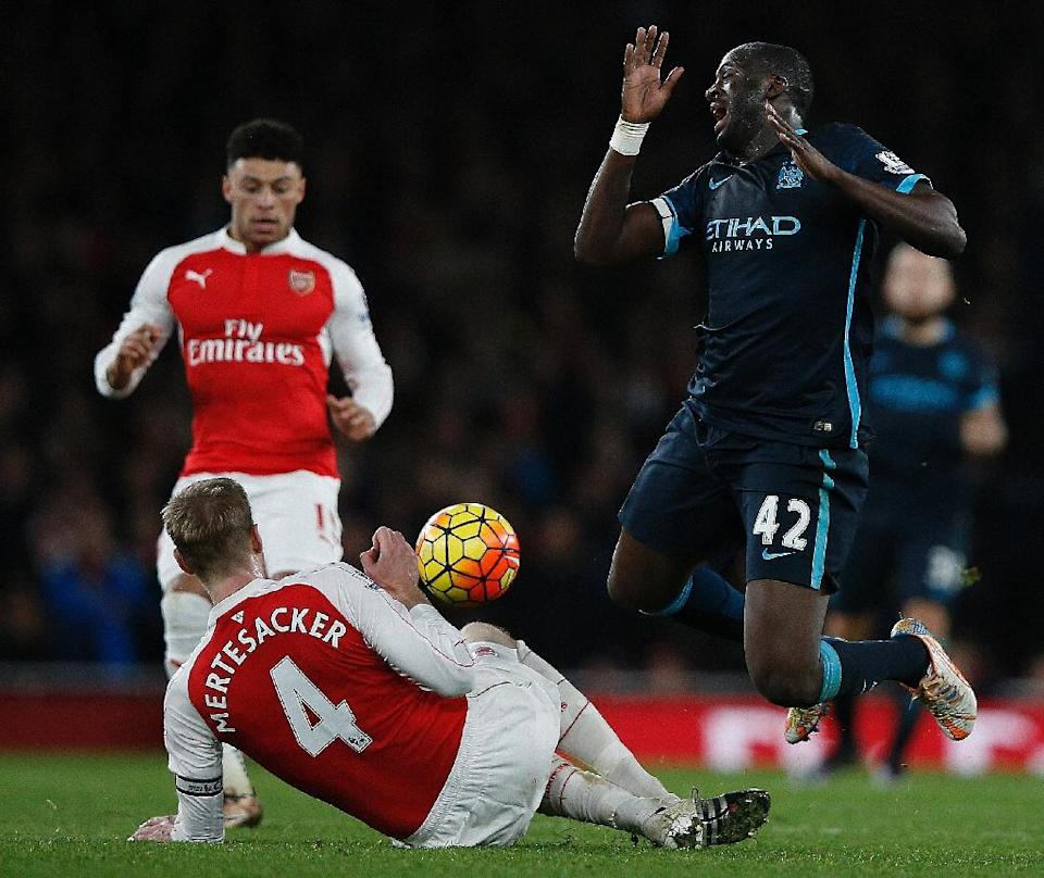 Arsenal's Per Mertesacker (C) and Manchester City's Yaya Toure during their Premier League match at Emirates Stadium on December 21, 2015 (AFP Photo/Adrian Dennis)