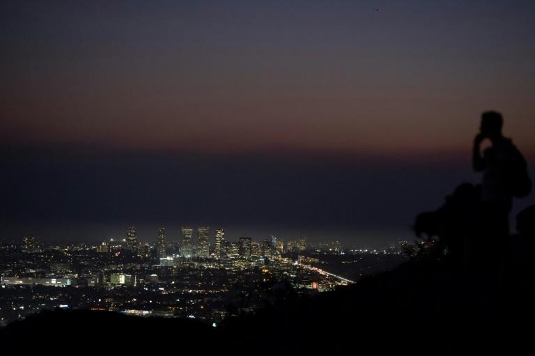 A hiker in Griffith Park looks toward the Century City neighborhood of Los Angeles where a layer of smoke from the Saddleridge fire hangs over tall buildings on October 11, 2019