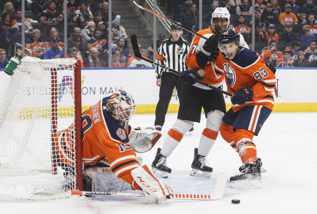 Philadelphia Flyers' Wayne Simmonds (17) and Edmonton Oilers' Matthew Benning (83) battle as Oilers goalie Mikko Koskinen (19) makes a save during first-period NHL hockey game action in Edmonton, Alberta, Friday, Dec. 14, 2018. (Jason Franson/The Canadian Press via AP)