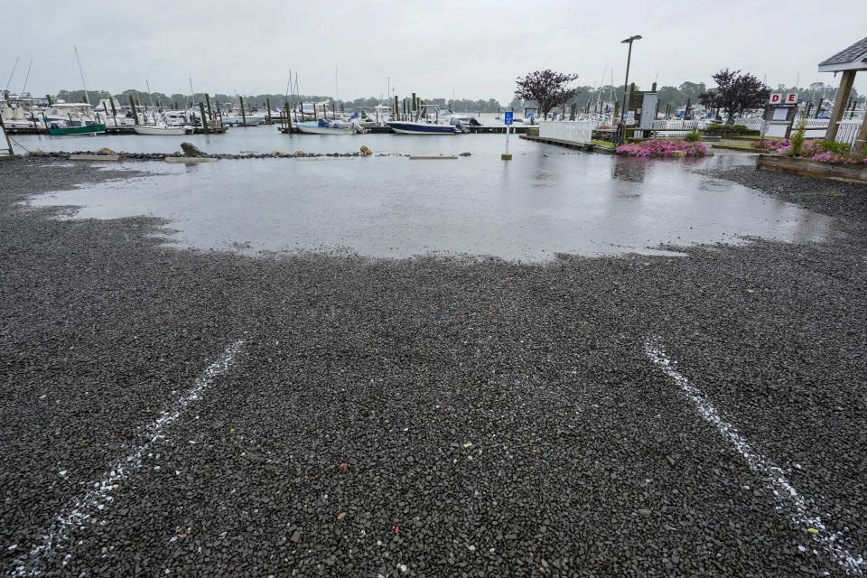 The parking lot of a marina starts to flood during high tide, Sunday, Aug. 22, 2021, in Branford, Conn., as Tropical Storm Henri affects the Atlantic coast. (AP Photo/Mary Altaffer)
