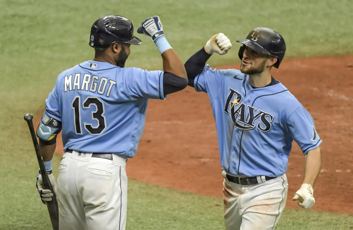 Tampa Bay Rays' Manuel Margot, left, greets Brandon Lowe, right, after Lowe's solo home run during the sixth inning of a baseball game Sunday, May 16, 2021, in St. Petersburg, Fla. (AP Photo/Steve Nesius)