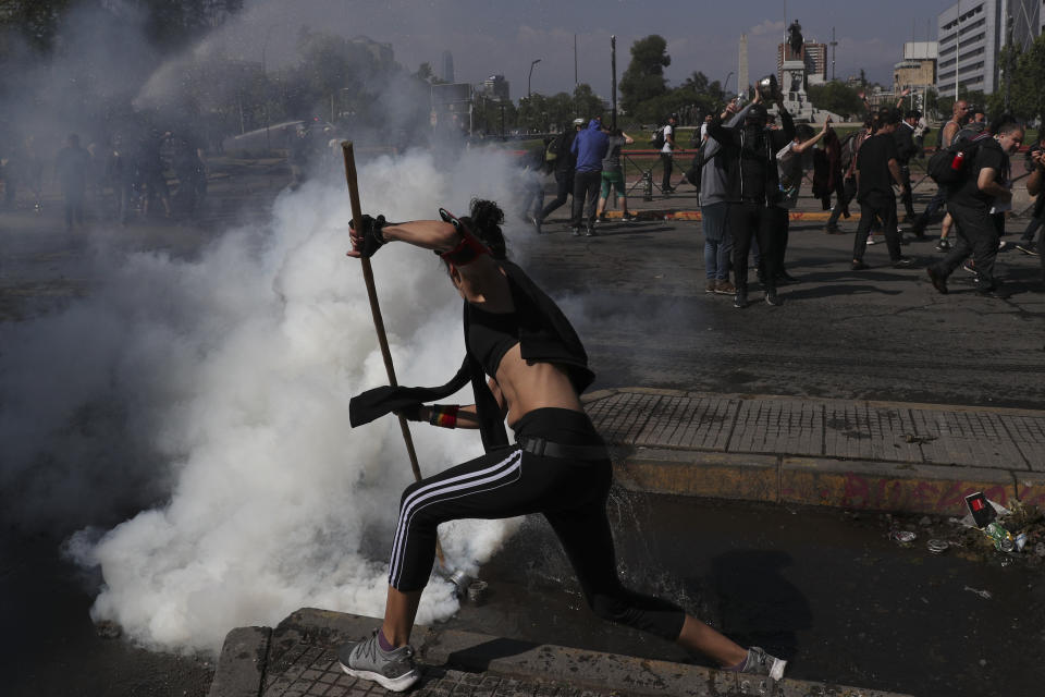 A protester intercepts a tear gas canister thrown by riot police in Santiago, Chile, Sunday, Oct. 20, 2019. Protests in the country have spilled over into a new day, even after President Sebastian Pinera cancelled the subway fare hike that prompted massive and violent demonstrations. (Photo: Esteban Felix/AP)