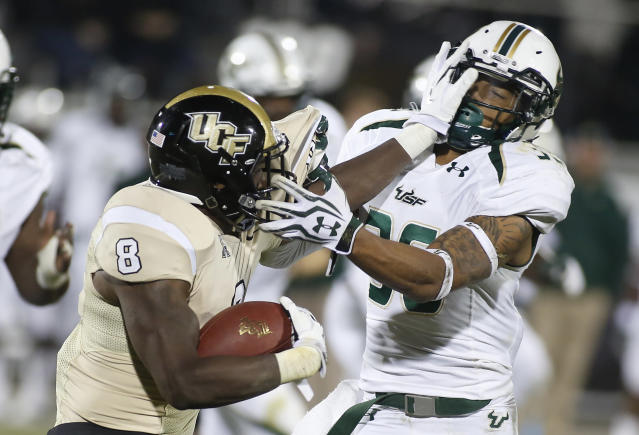 Central Florida running back Storm Johnson (8) stiff-arms South Florida defensive back Nate Godwin (36) during the second half of an NCAA college football game Friday, Nov. 29, 2013, in Orlando, Fla. UCF won 23-20. (AP Photo/Reinhold Matay