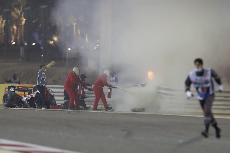 Staff extinguish flames from Haas driver Romain Grosjean of France's car after a crash during the Formula One race in Bahrain International Circuit in Sakhir, Bahrain, Sunday, Nov. 29, 2020. (Tolga Bozoglu, Pool via AP)