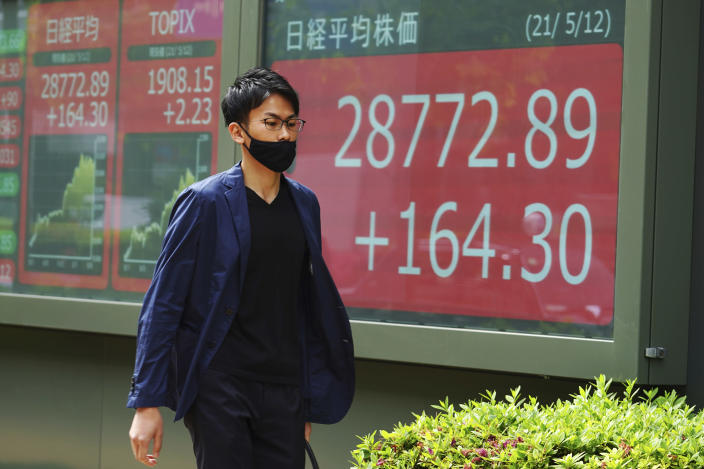 A man wearing a protective mask walks in front of an electronic stock board showing Japan's Nikkei 225 index at a securities firm Wednesday, May 12, 2021, in Tokyo. Asian stock markets retreated Wednesday as investors looked ahead to U.S. data they worry will show inflation is picking up.(AP Photo/Eugene Hoshiko)