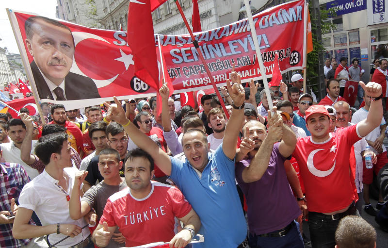 CORRECTS TO PRIME MINISTER - Supporters of Turkish Prime Minister Recep Tayyip Erdogan are waving flags and hold a banner during a demonstration in Vienna, Austria, Sunday, June 23, 2013. Several thousand protesters gathered in Vienna to support Erdogan and his policy. (AP Photo/Herwig Prammer)