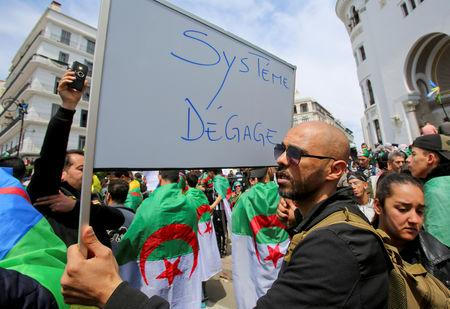 """A man carries a sign reading """"System, get out"""" during a protest seeking the departure of the ruling elite in Algiers, Algeria April 12, 2019. REUTERS/Ramzi Boudina"""