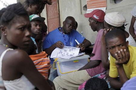 An enumerator with The International Organization for Migration (IOM) interviews people who returned from the Dominican Republic, at a camp for returned Haitians and Haitian-Dominicans, near the border between the Dominican Republic and Haiti, in Malpasse, August 3, 2015. REUTERS/Andres Martinez Casares