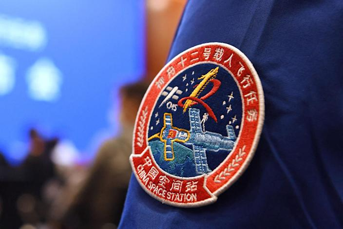 Image: A staff member of the Jiuquan Satellite Launch Centre wears the logo of China's new space station during a press conference about the first crewed mission to the station, China (Greg Baker / AFP - Getty Images)