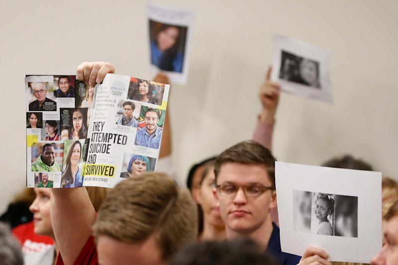 Harsher gun laws supporters hold us photos of gun violence victims during a meeting of the Senate Judiciary Committee on Thursday (AP)