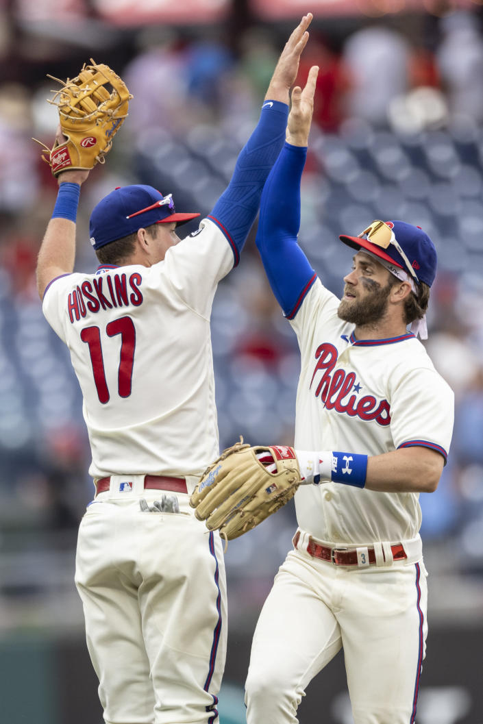 Philadelphia Phillies first baseman Rhys Hoskins (17) and right fielder Bryce Harper celebrate after they defeated the Miami Marlins in a baseball game, Sunday, July 18, 2021, in Philadelphia. (AP Photo/Laurence Kesterson)