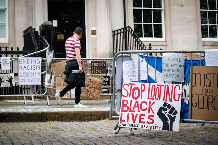 """<i>Protest signs posted outside the U.S. Consulate General in Edinburgh, Scotland, in response to the police killing of George Floyd. One reads: """"Stop looting Black lives. End police brutality."""" </i>"""