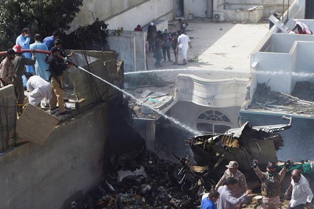 Policemen spray water on the part of a Pakistan International Airlines aircraft after it crashed at a residential area in Karachi on May 22, 2020. - A Pakistan passenger plane with more than 100 people believed to be on board crashed in the southern city of Karachi on May 22, the country's aviation authority said. (Photo by Asif HASSAN / AFP) (Photo by ASIF HASSAN/AFP via Getty Images)