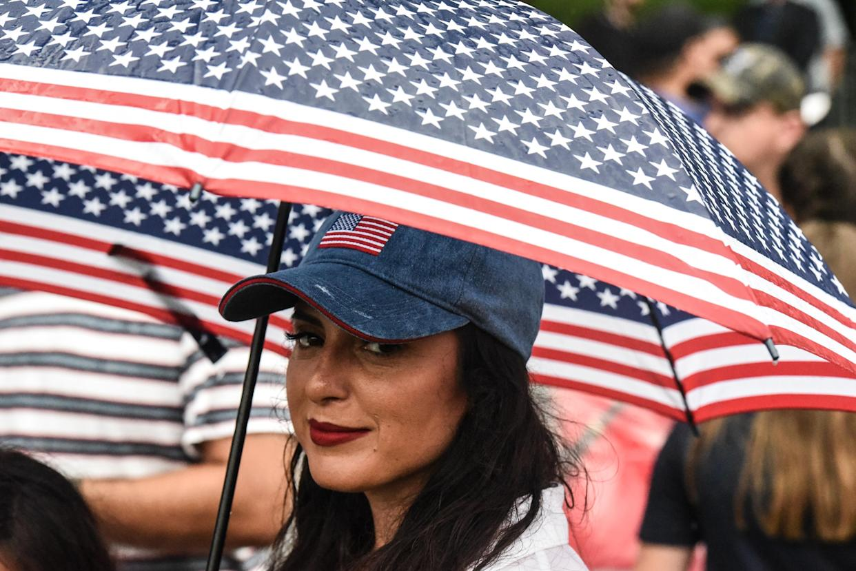 A woman with a red, white and blue umbrella is seen on the National Mall while President Donald Trump gives his speech during Fourth of July festivities on July 4, 2019 in Washington, DC. (Photo: Stephanie Keith/Getty Images)