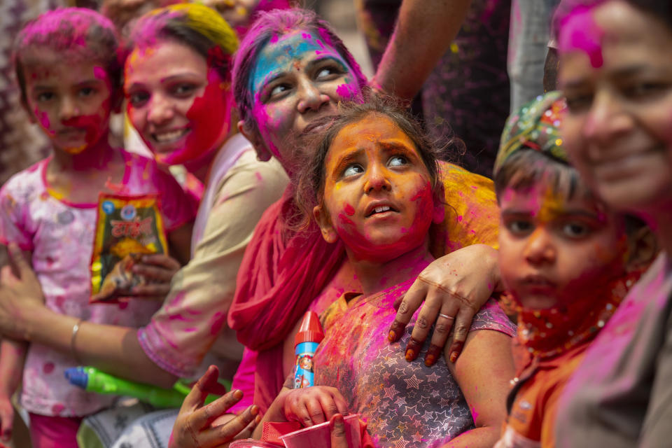 Indians smeared in color participate in Holi festival celebrations in Gauhati, India, Monday, March 29, 2021. Hindus threw colored powder and sprayed water in massive Holi celebrations Monday despite many Indian states restricting gatherings to try to contain a coronavirus resurgence rippling across the country. (AP Photo/Anupam Nath)