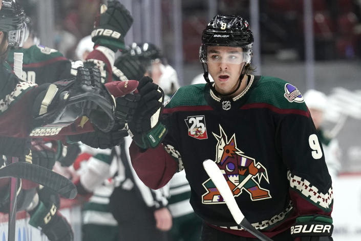 Arizona Coyotes right wing Clayton Keller celebrates with teammates after scoring a goal against the Minnesota Wild during the third period during an NHL hockey game Friday, March 5, 2021, in Glendale, Ariz. Minnesota won 5-1. (AP Photo/Rick Scuteri)