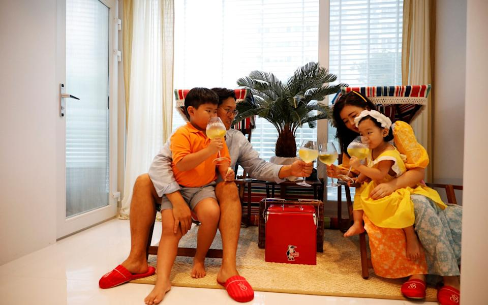 Yoon Seok-min and Kim Hyo-jung drink a beverage with their children at their home in Yongin - Reuters