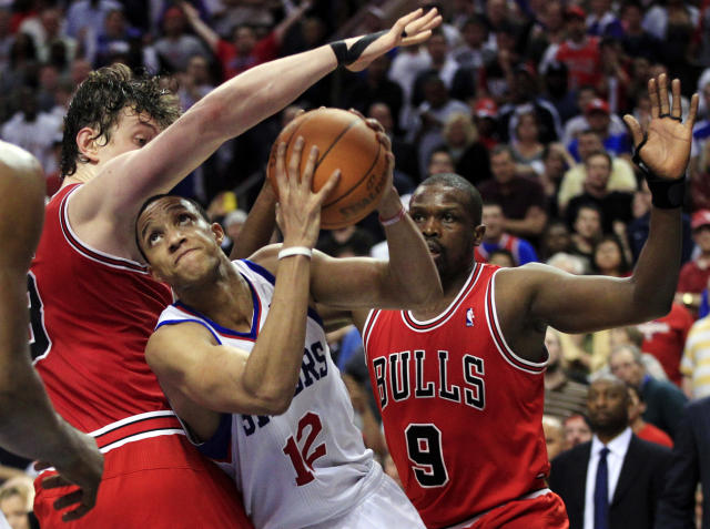 Philadelphia 76ers' Evan Turner (12) fights his way to the basket past Chicago Bulls' Omer Asik, of Turkey, and Luol Deng, (9) late in the fourth quarter of Game 3 in an NBA basketball first-round playoff series in Philadelphia, Friday, May 4, 2012. The 76ers won 79-74. (AP Photo/Mel Evans)