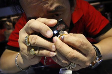 Store employee Jeffrey inspects a diamond ring that the store had acquired at a Cash Converters used goods store in Singapore