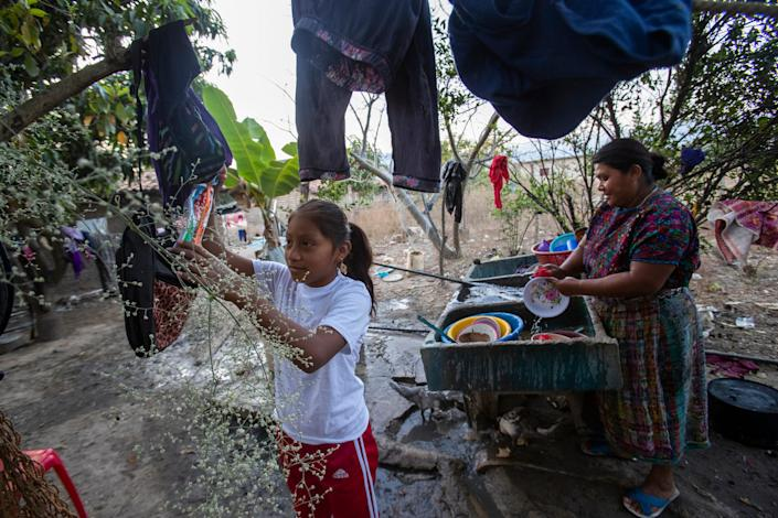 Melissa Sical and her mother, Maria Elvira Ramos, wash dishes using well water in Baja Verapaz, Guatemala, in early March 2020. Sical and her father traveled to the U.S. border during the summer of 2019, where they were subjected to the Migrant Protection Protocols and required to wait in Juárez two months for a U.S. court hearing.