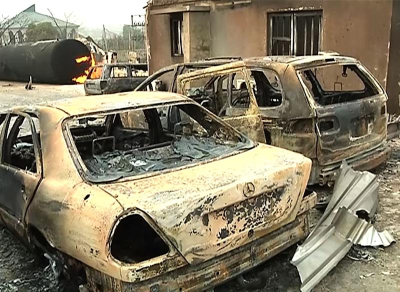 A burning cistern and burnt cars in the aftermath of a blast at an industrial gas plant in Nnewi, southeast Nigeria, in a frame grab made on December 25, 2015 from a video shot the same day by TV Continental (AFP Photo/)